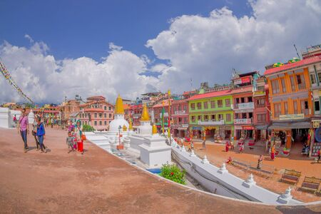 KATHMANDU, NEPAL OCTOBER 15, 2017: Unidentified people walking close to the heritage monument Boudhanath stupa and its colorful flags in daylight with bue sky, following full restoration after 2015 earthquake damage. Kathmandu, Nepal, fish eye effect. Editorial