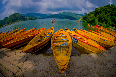 phewa: POKHARA, NEPAL - NOVEMBER 04, 2017: Close up of wooden yellow boats in a row at Begnas lake in Pokhara, Nepal, fish eye effect
