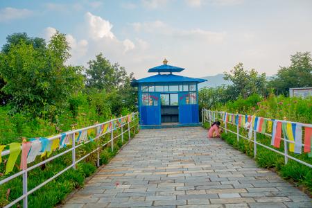 phewa: POKHARA, NEPAL, SEPTEMBER 04, 2017: Close up of a stoned path with a blue hut close to a Phewa Tal, the brilliant-white World Peace Pagoda in Pokhara is a massive Buddhist stupa