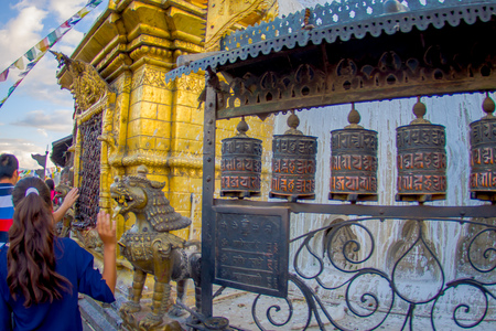 KATHMANDU, NEPAL OCTOBER 15, 2017: Unidentified people walking at outdoors close to Nepalese religious carvings and prayer wheels at Swayambhu Temple also known as the Monkey Temple in Kathmandu, Nepal