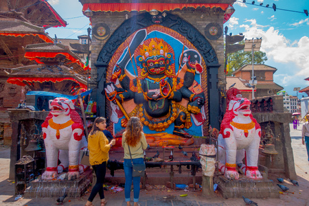 KATHMANDU, NEPAL OCTOBER 15, 2017: Unidentified people at outdoors close to a stoned sculptures with a carved wall with a god, located in Durbar square in Kathmandu, capital of Nepal Editorial