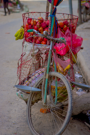 rickshaw: Close up of a bike with some apples fruits inside of a metallic basket in the street in historic center of city, in Kathmandu, Nepal. Largest city of Nepal, its historic center, a population of over 1 million people Stock Photo