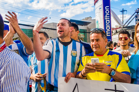 QUITO, ECUADOR - OCTOBER 11, 2017: Close up of Argentina fans wearing his official football shirt and supporting his team in outdoors, screaming and jumping