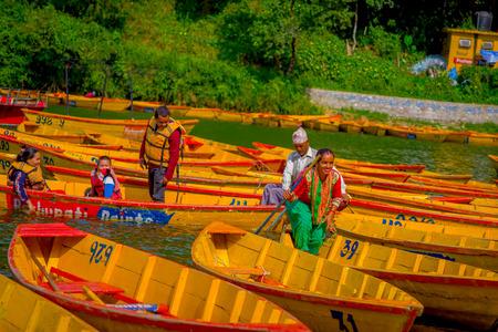 phewa: POKHARA, NEPAL - NOVEMBER 04, 2017: Family paddling the boats in the lake with at Begnas lake in Pokhara, Nepal Editorial