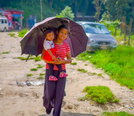 POKHARA, NEPAL - NOVEMBER 04, 2017: Unidentified woman holding a baby in her arms and protecting from the sun using a purple umbrella in Pokhara, Nepal