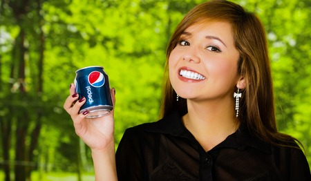 Quito, Ecuador May, 06, 2017: Portrait of beautiful smiling young woman holding a pepsi in blurred green background.