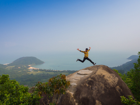 HOIAN, VIETNAM, SEPTEMBER, 04 2017: Unidentified man jumping over a huge rock with a beautiful view of the coastline of Danang, Vietnam, in a sunrise from the top of a mountain.