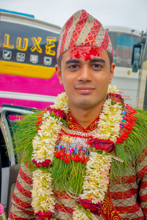 POKHARA, NEPAL OCTOBER 10, 2017: Portrait of a handsome man wearing flowers around his neck and wearing typical clothes and villagers celebrating a nepalese wedding in Besisahar, Nepal