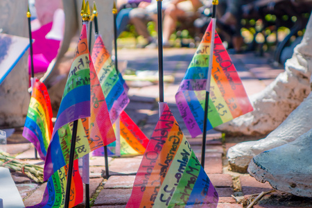 ORLANDO, USA - MAY 05, 2017: Small gay flags in the ground, place where Omar Mateen, killed 49 people and wounded 53 others in a terrorist attack hate crime in a gay nightclub in Orlando, Florida, United States