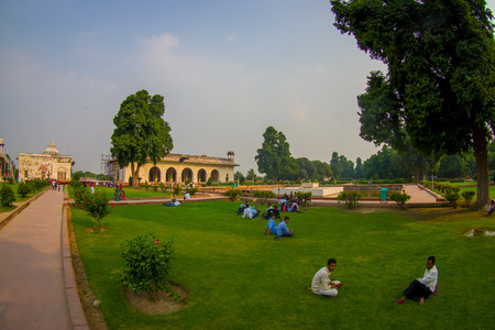 DELHI, INDIA - SEPTEMBER 25 2017: Unidentified people sitting in the grass enjoying the view of the Sawan or Bhadon Pavilion in Hayat Baksh Bagh of Red Fort at Delhi. Decorated with white marble, depicting Mughal artwork, fish eye effect Stok Fotoğraf - 90353948