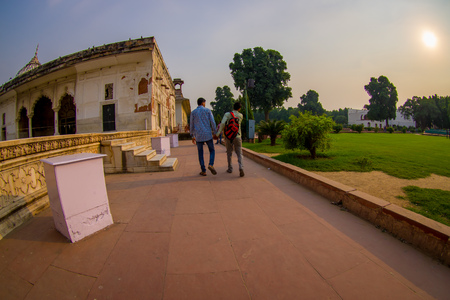 DELHI, INDIA - SEPTEMBER 25 2017: Unidentified gay couple holding their hands and walking around Inlaid marble, columns and arches, Hall of Private Audience or Diwan I Khas at the Lal Qila or Red Fort in Delhi, India, fish eye effect