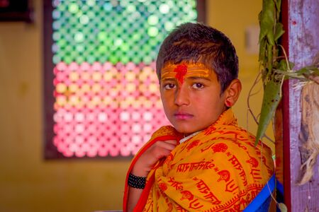 KATHMANDU, NEPAL - SEPTEMBER 04, 2017: Portrait of young Nepalese boy wearing typical clothes and some orange and red color in his forehead, in Nepal.