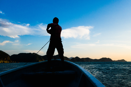 TAGANGA, COLOMBIA - OCTOBER 19, 2017: Shadow of unidentified man inside of a boat during a sunset at the beautiful caribbean beach in Taganga, Colombia