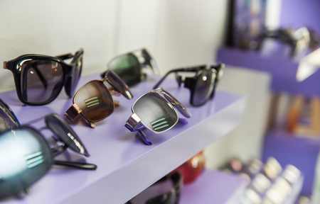 Close up of assorted beautiful glasses in optician store inside of purple showcase, in a blurred background