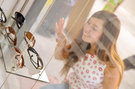 9b8e7d7a010da5 Mooie jonge vrouw die verschillende glazen in optische opslag binnen van  showcase op een vage achtergrond