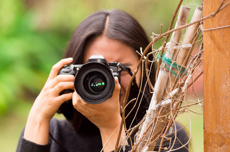 Young woman stalking and taking pictures with her camera, at outside