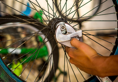 Close up of bicycle mechanic using a wrench and repairing the wheel in a workshop, in blurred background Stock Photo