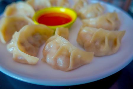 おいしいネパールの伝統的なスナック、チキンMoMoは白いプレートにスパイシーで酸っぱいソースを添えて提供 写真素材
