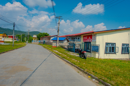 POKHARA, NEPAL - OCTOBER 06 2017: Outdoor view of different buildings with a pavement street, with some cables lines in Pokhara, Nepal Editorial