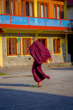 POKHARA, NEPAL - OCTOBER 06 2017: Unidentified Buddhist monk teenagrer playing with a small piece of fabric over a stoned ground at outdoors at the Tashi refugee settlement in Pokhara, Nepal