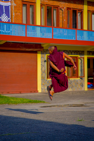 POKHARA, NEPAL - OCTOBER 06 2017: Unidentified Buddhist monk teenagrer playing and jumping over a stoned ground at outdoors at the Tashi refugee settlement in Pokhara, Nepal