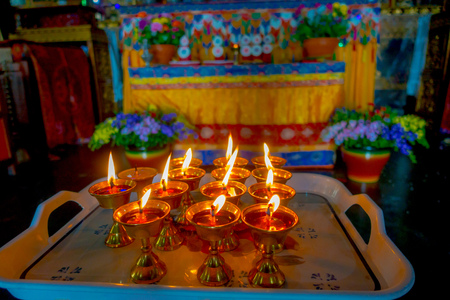 POKHARA, NEPAL - OCTOBER 06 2017: Close up of some candels inside of a goblet over a plastic tray in Thrangu Tashi Choling Monastery in Kathmandu, Nepal