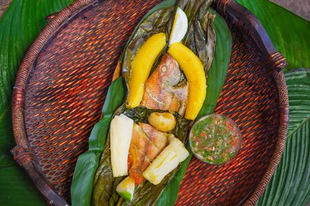 Above view of delicious typical amazonian food, fish cooked in a leaf with yucca and plantain, bowl of salad, served in a wooden platen over a wooden table