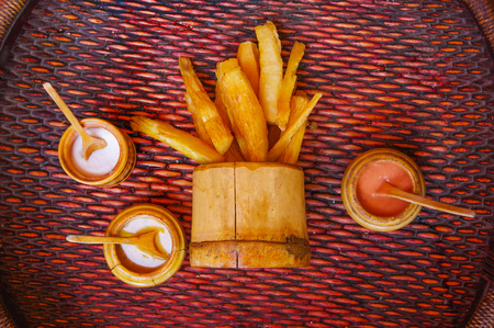 Above view of delicious fried yucca inside of a wooden bowl with assorted sauces, over a wooden table