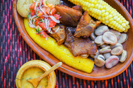 Close up of delicious hornado, ecuadorian traditional typical andean food served with corn, potato, salad, plantain and broad beans in a clay plate over a table