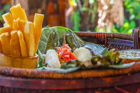 Close up of delicious typical amazonian food, fish cooked in a leaf with yucca and plantain, bowl of salad and fried yucca, served in a wooden platen over a wooden table