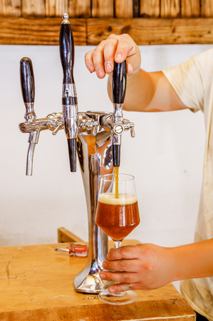 Barman hand at beer tap pouring a draught lager beer serving in a restaurant or pub, in a blurred background