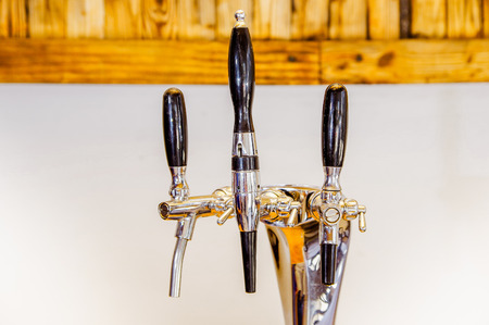 Close up of multiple beer taps located over a wooden table in a blurred background