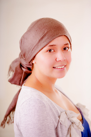 Close up of a woman with cancer wearing headscarf, having positive attitude, in a blurred background Foto de archivo