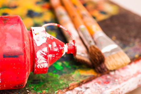 Close up of paint brushes with a red plastic color over a color palette in a studio, in a blurred background