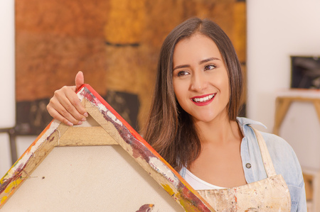 Beautiful smiling woman painter holding in her hands an empty frame in a studio paint background, art classes for adults, education concept Stock Photo
