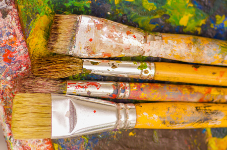 Top view of paint brushes over a color palette in a blurred background