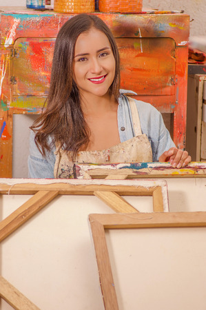 Beautiful woman painter behind of empty frame, in a studio paint background Stock Photo