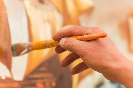 Close up of man hand husing a paint brush over a color palette in art studio, in a blurred background