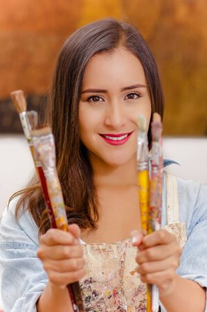Beautiful young woman painter with paint brush in hands, in a blurred background