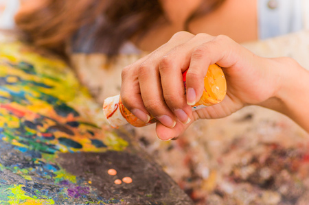 Cose up of woman hand with orange flask, over a color palette in a blurred background