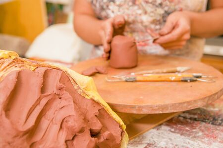 Close up of a clay mass with a blurred woman ceramist behind working on sculpture on wooden table in workshop, in a blurred background