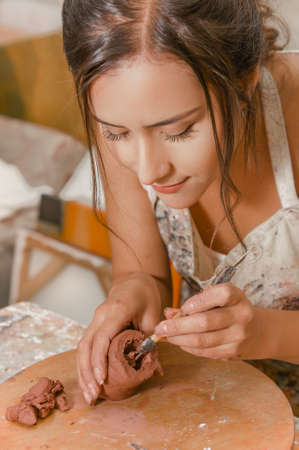 Close up of beautiful woman ceramist, very focus working on sculpture on wooden table in workshop, in a blurred background