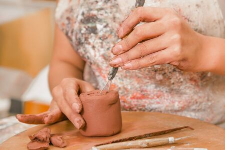 Close up of woman ceramist hands working with a tool over a sculpture on wooden table in workshop