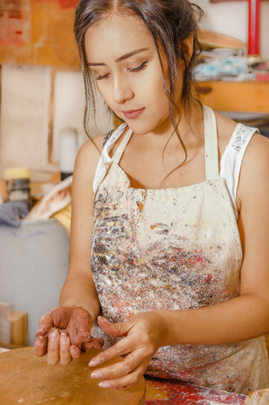Close up of woman ceramist working on sculpture on wooden table in workshop Stock Photo