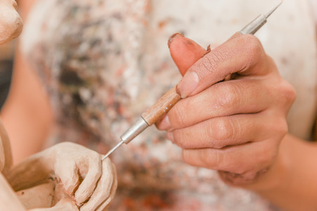 Close up of woman ceramist hands holding a tool and working on sculpture details on wooden table in workshop Stock Photo