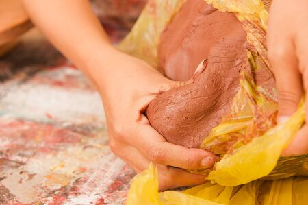 Close up of a woman hand manipulating a clay mass on wooden table in workshop, in a blurred background Stock Photo