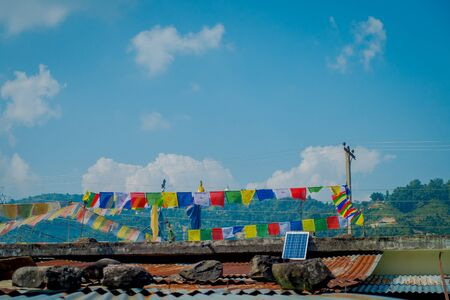 POKHARA, NEPAL - OCTOBER 06 2017: Beautiful outdoor view of colorful flags over a roots of a building, in Pokhara, Nepal