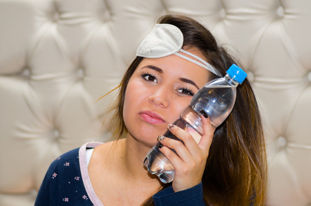 Drunk woman with a sleeping eye mask in her head and with a bottle of water pressing in her face using her other hand, hangover concept Stock Photo