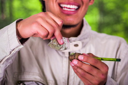Close up of a man addict holding in his hands a pipe and adding marihuana to smoke, trafficking, crime, in a blurred background