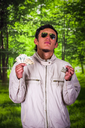 Close up of a man dealer wearing dark sunglases, and holding in his hands money and drug in his other hand, trafficking, crime, in a blurred background